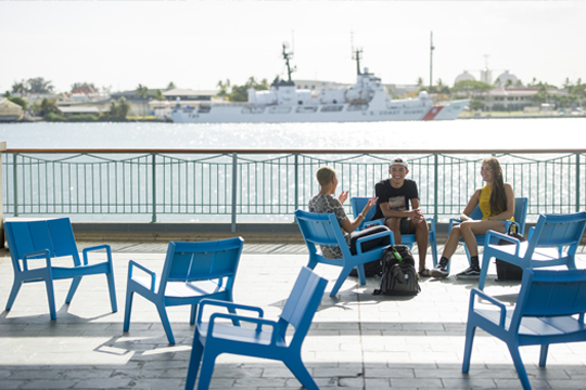 3 students chatting on blue chairs near the pier at Aloha Tower. Behind them, a boat is in the water.